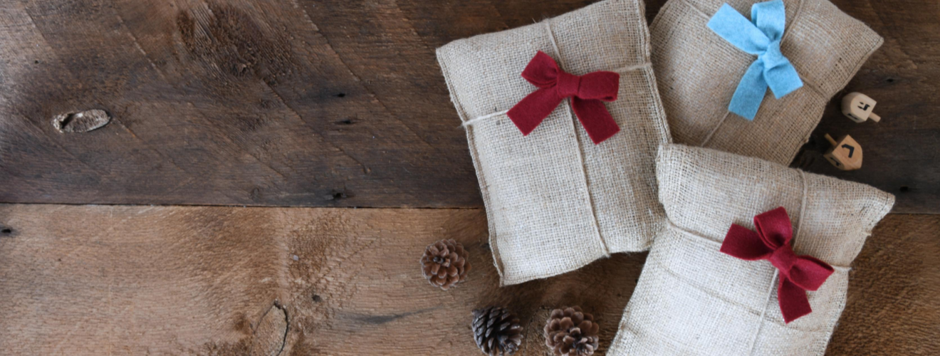 picture showing a photo of three wrapped gifts on a wooden background.